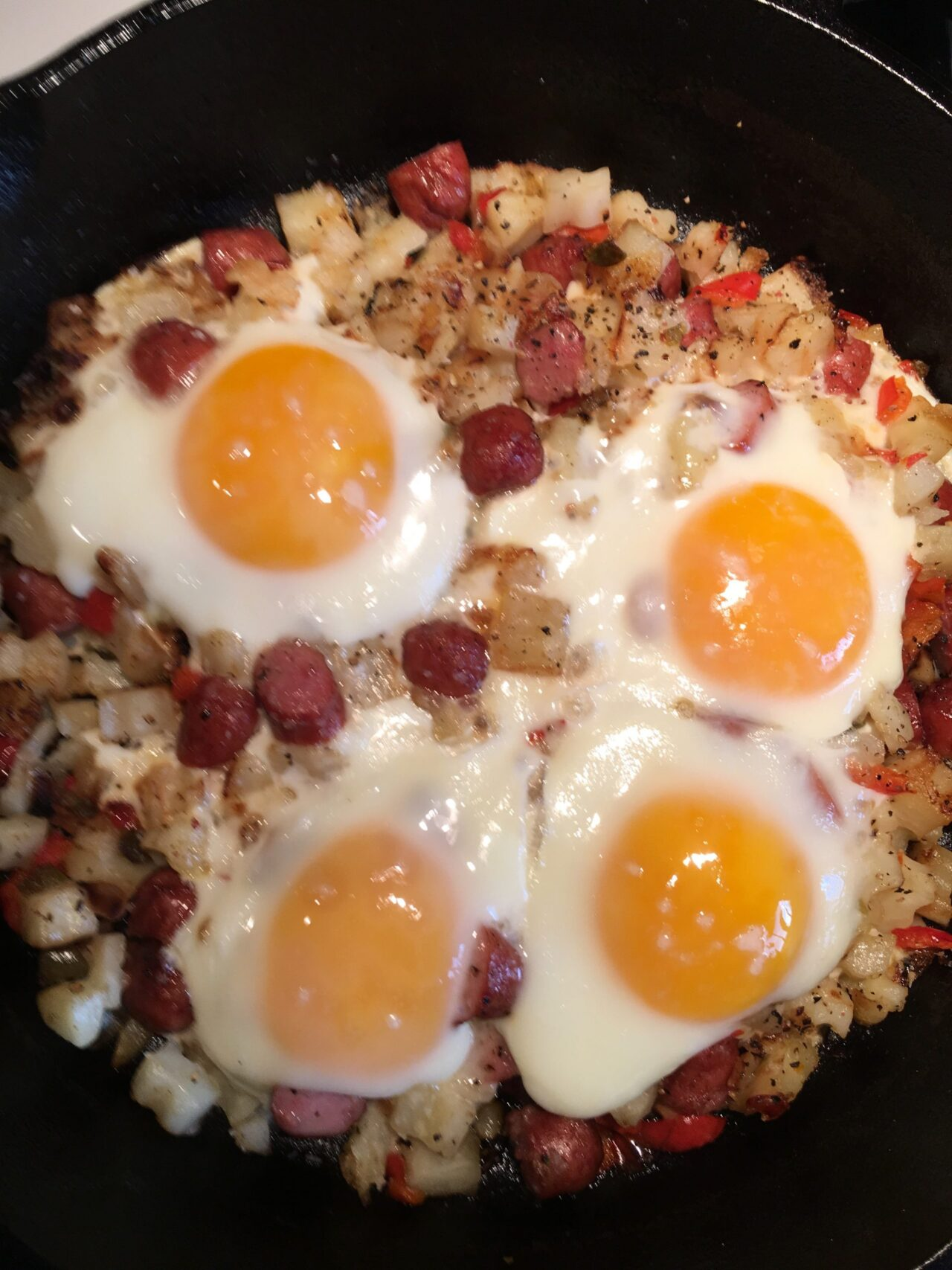 Cooked breakfast hash with eggs on top